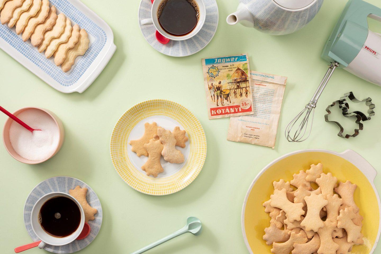Biscuiți cu ghimbir pe un platou de prăjituri și un set de cafea în culori pastelate.