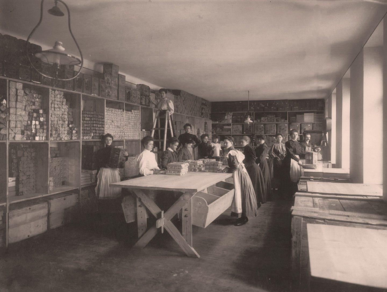 Fotografie alb-negru: Muncitori ambalând boia de ardei dulce măcinată Kotányi în 1881