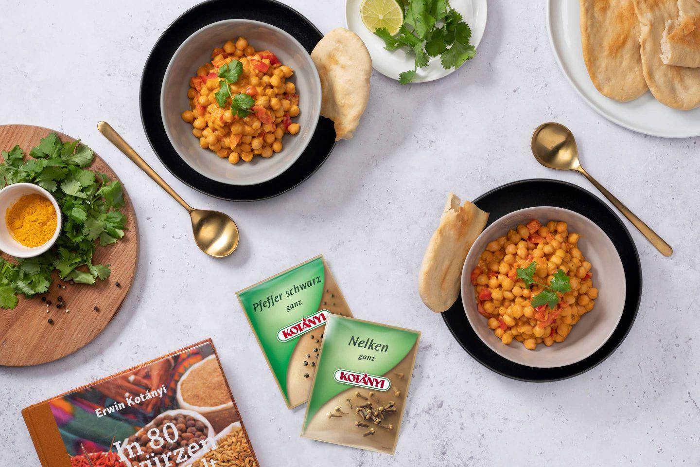 Curry cu năut cu pâine naan alături de plicuri cu piper negru și cuișoare întregi.