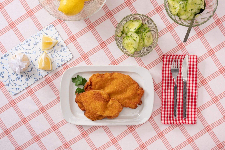 Două Șnițele vieneze servite cu salată de castraveți decorată cu mărar.
