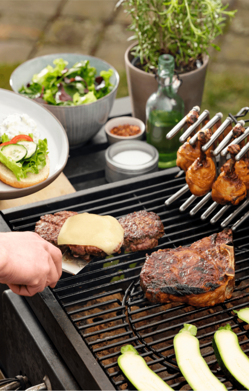 Burger patties, chicken drumsticks on a pot lid holder and chops on the grill.